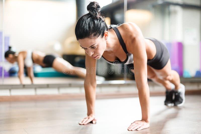 Spiervrouw die Plankoefening in Geschiktheidsstudio doen stock fotografie