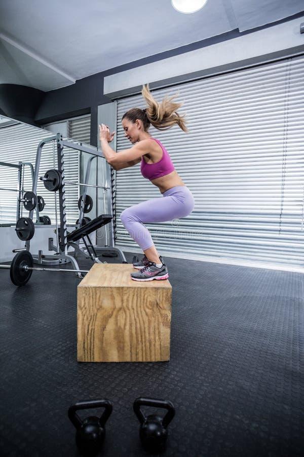 Spiervrouw die springende hurkzit doen stock foto