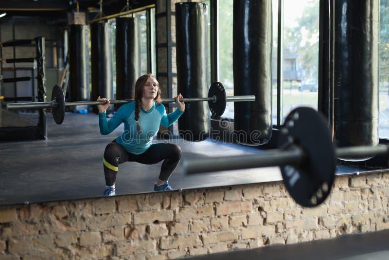 Spiervrouw in een gymnastiek die hurkzit doen royalty-vrije stock foto's