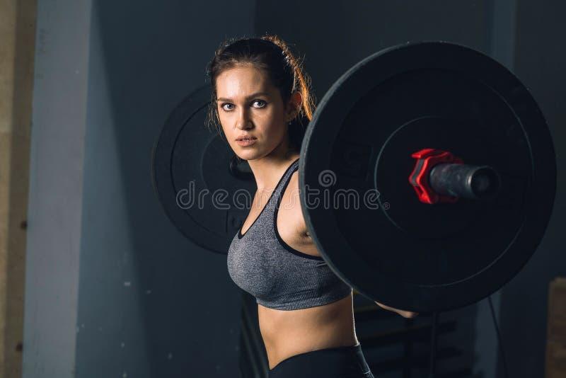 Spiervrouw in een gymnastiek die zwaargewicht oefeningen met barbell doen stock foto