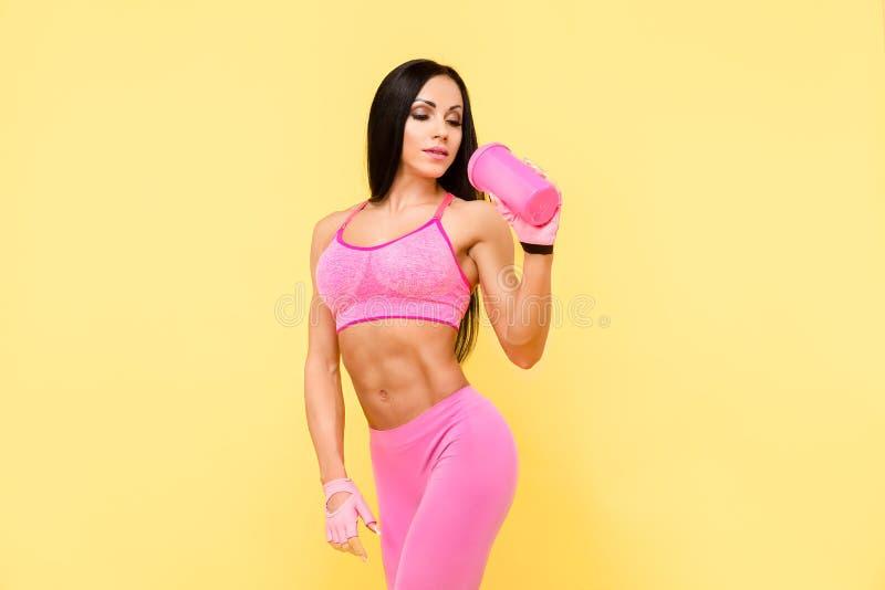 Spiervrouw in het fitnesswear drinken van de fles stock foto's
