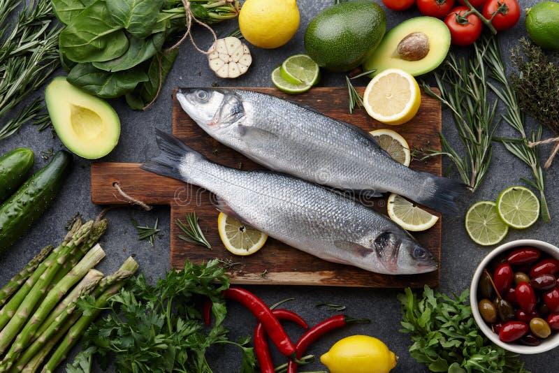 Spigola ed ingredienti crudi freschi per cucinare immagine stock