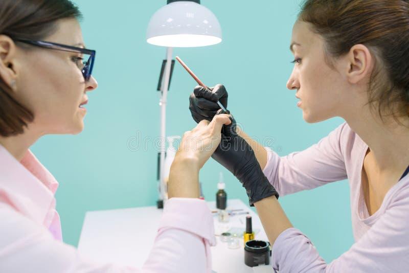Spijker en handzorg in schoonheidssalon Jonge vrouw die professionele manicure doen stock afbeeldingen