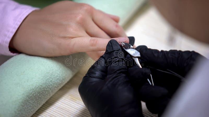 Spijkermeester die in handschoenen opperhuid met tang, hygiëne in schoonheidssalon verwijderen stock foto's