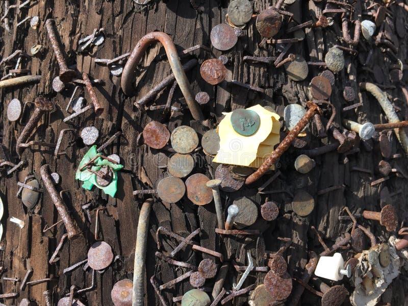 Spijkers en nietjes en willekeurige die beetjes van materiaal in een lamppost worden gepost royalty-vrije stock foto's