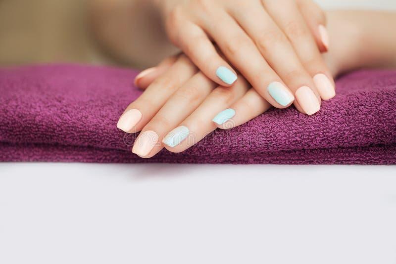 Spijkers in het kuuroord Mooie manicure Kosmetische procedures met handen en spijkers Het liggen op een geweer Het concept schoon stock foto's
