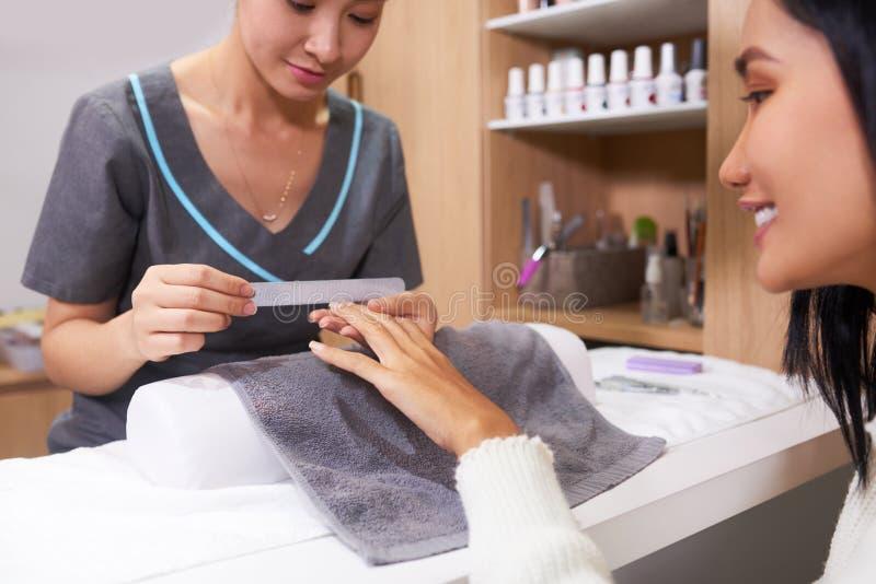 Spijkerspecialist die manicure doen stock afbeelding