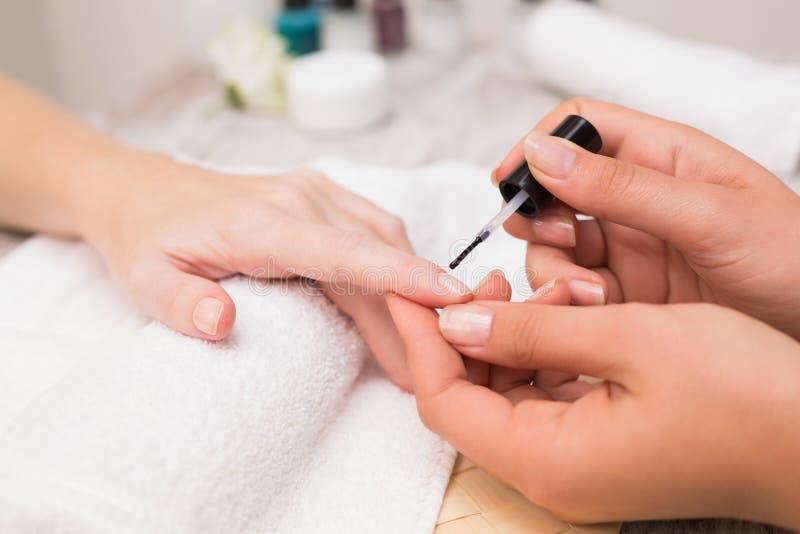 Spijkertechnicus die klant een manicure geven stock afbeeldingen