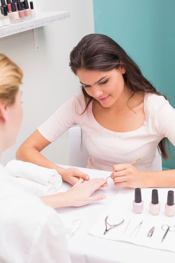 Spijkertechnicus die klant een manicure geven royalty-vrije stock fotografie
