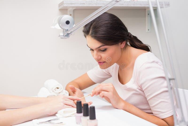 Spijkertechnicus die klant een manicure geven stock foto's