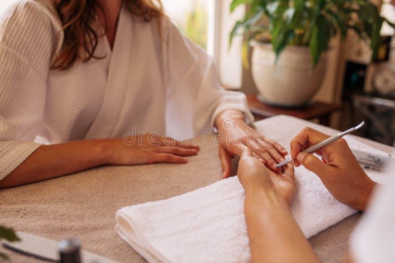 Spijkertechnicus die klant een manicure geven bij schoonheidssalon stock foto