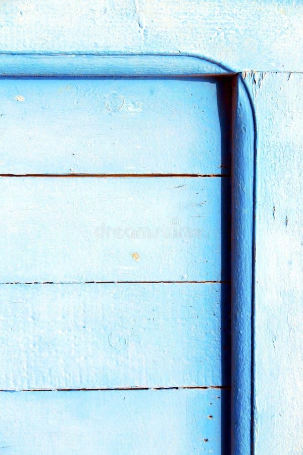 spika avrivet i den rostiga blåa wood dörren arkivfoto