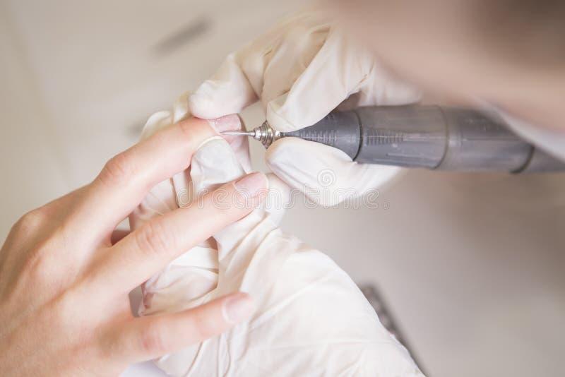 Spika förlagen i rubber handskar gör manikyr genom att använda manikyrmachin arkivfoton