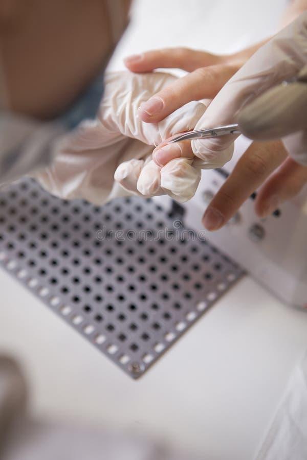 Spika förlagen i rubber handskar gör manikyromsorgnagelbandet på en w royaltyfri foto