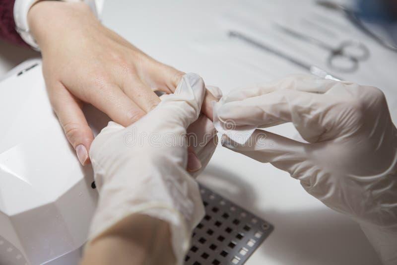 Spika förlagen i rubber handskar gör manikyromsorgnagelbandet på en w arkivfoto
