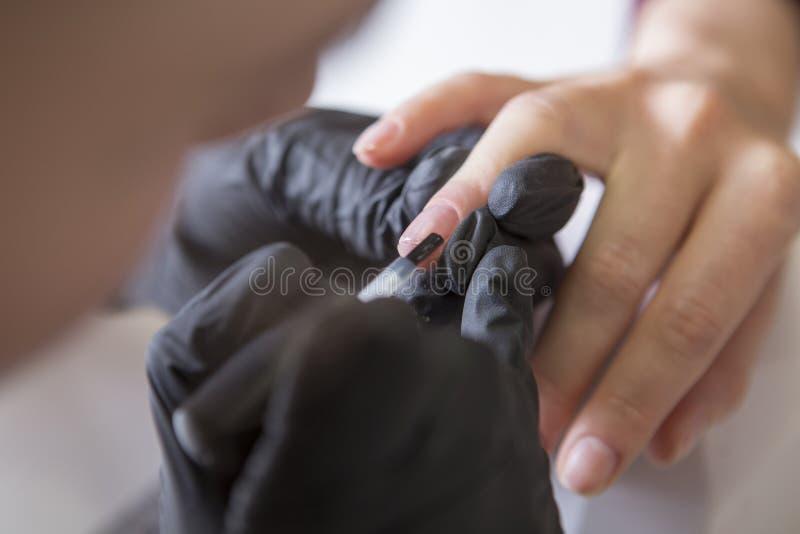 Spika förlagen i rubber handskar gör manikyromsorgnagelbandet på en w royaltyfri bild