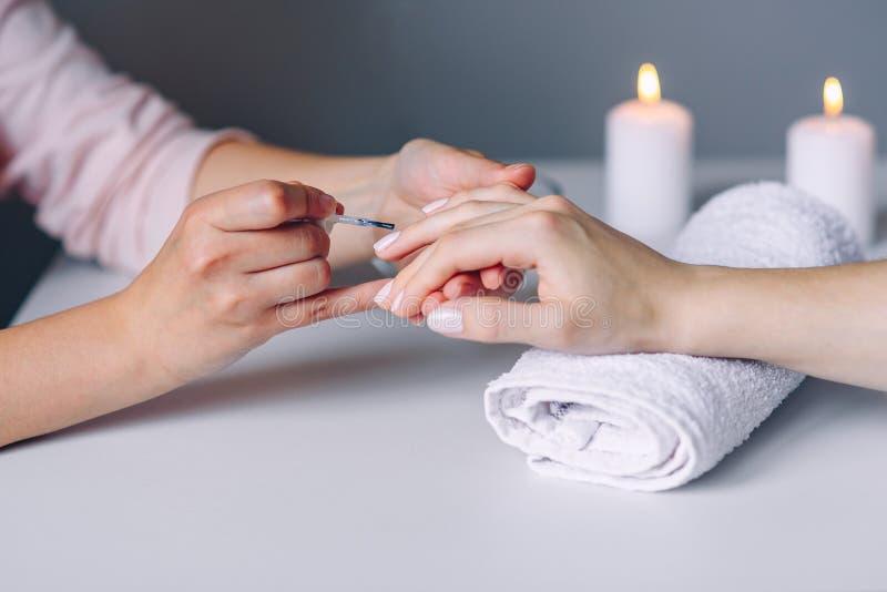 Spika omsorg och manikyr Spikar den sunda naturliga kvinnan f?r closeupen i sk?nhetsalong Manikyristen som handen m?lar klienten, arkivbild