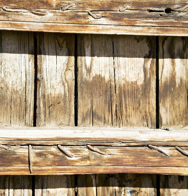 Spika smutsig avriven målarfärg i den bruna wood dörren och den rostiga yelloen fotografering för bildbyråer