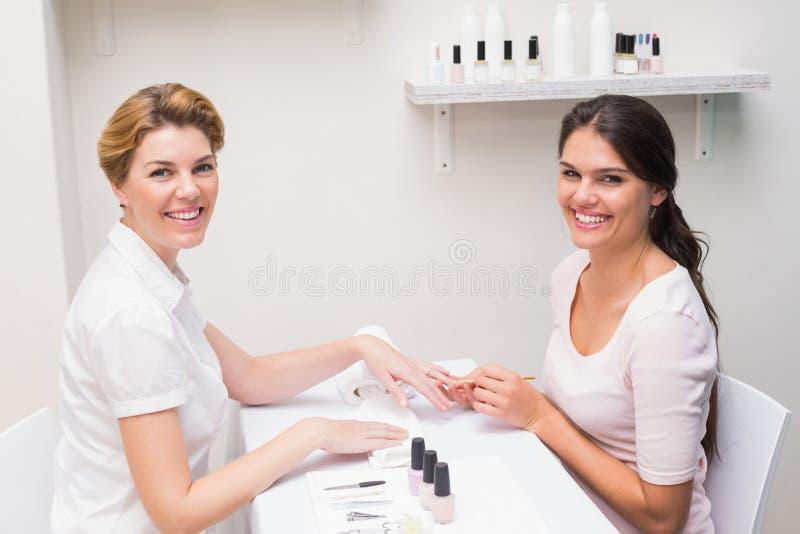 Spika teknikeren som ger kunden en manikyr royaltyfri foto