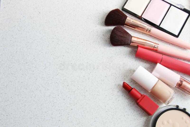 Spikar den ansikts- rodnaden för makeuppulverfundament med röd läppstift och Hilight den näcka signalen marmorerar på texturbakgr royaltyfri bild