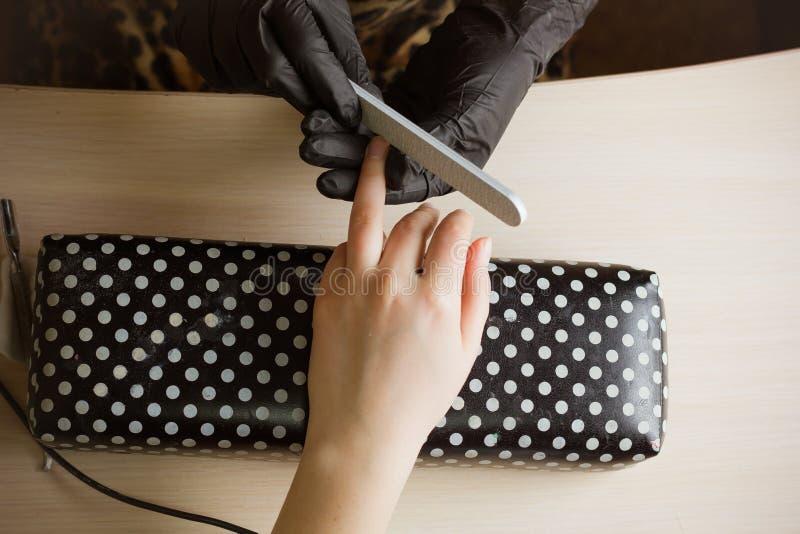 Spikar det polerande pekfingret för manikyristen för manikyr in skönhetsalongen Moment av manikyrprocessen arkivfoton