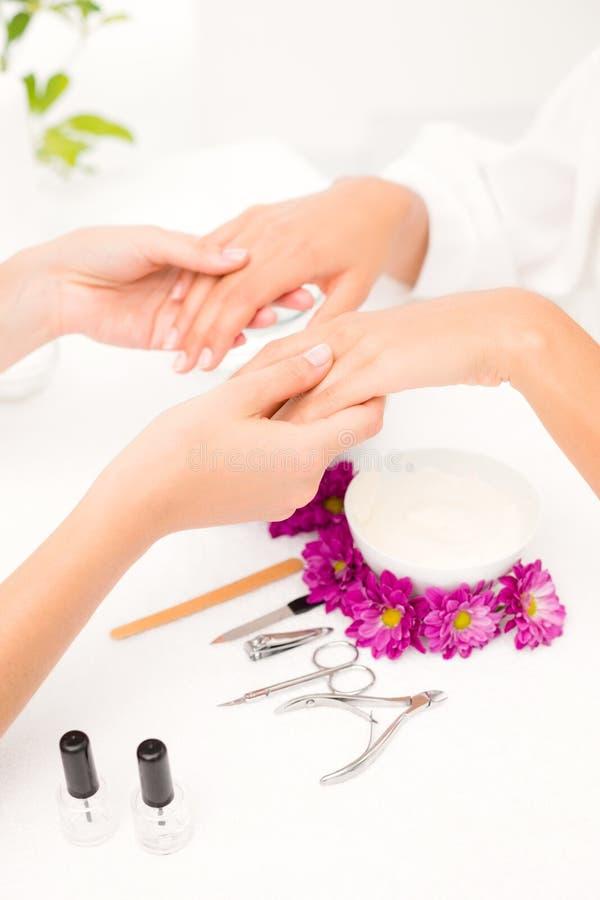Spikar kvinnliga klienter för kosmetologarkivering på brunnsortskönhetsalongen arkivbild