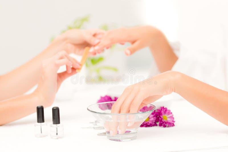 Spikar kvinnliga klienter för kosmetologarkivering på brunnsortskönhetsalongen arkivbilder