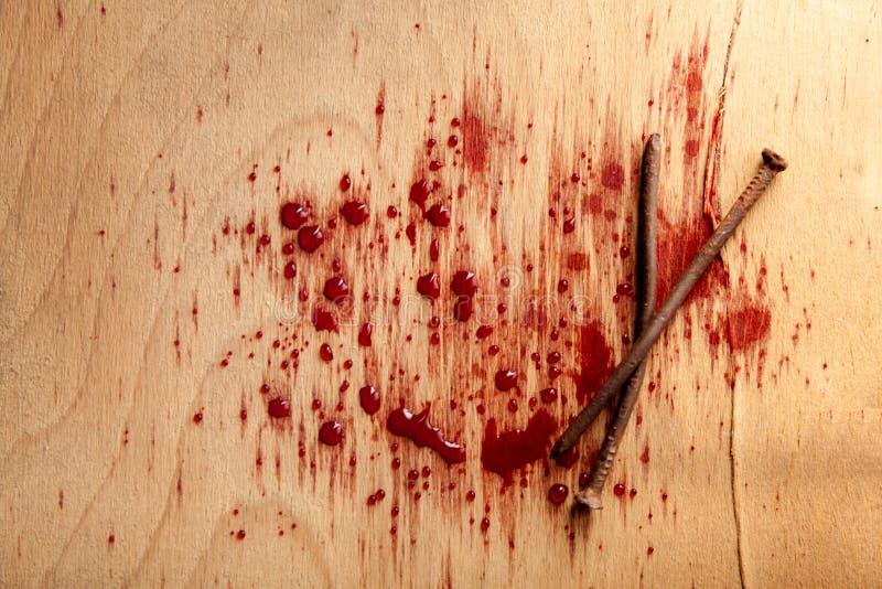 Spikar med blod på det wood skrivbordet royaltyfri bild