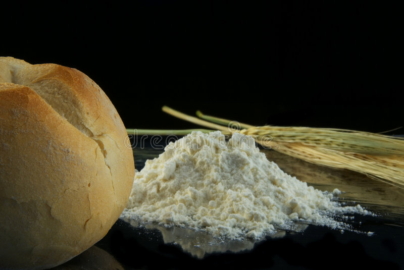 From spike to bread. Spike made to flour to bread on black background stock photography