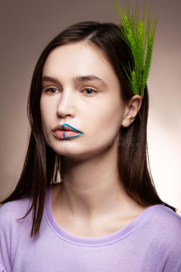 Dark-haired model posing with green spikelet in her hair royalty free stock image