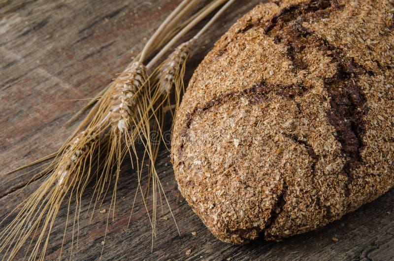 Spikelets και ψημένο το ψωμί σε ένα ξύλινο υπόβαθρο στοκ φωτογραφία