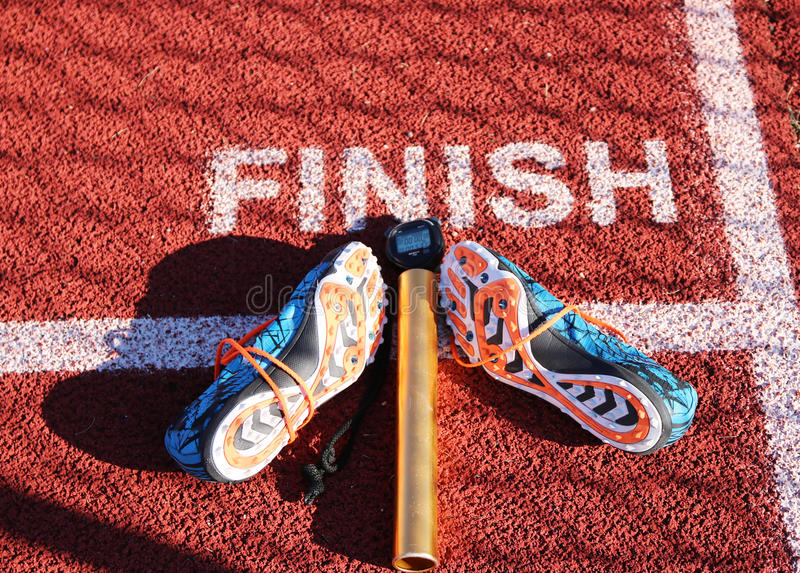 Spikes, baton and stop watch at the finish line on a track. Finish line of a track with spikes, a baton and and a stop watch on it royalty free stock image