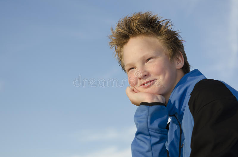Spiky hairstyle. Pleased teen with spiky hairstyle against blue sky background stock images