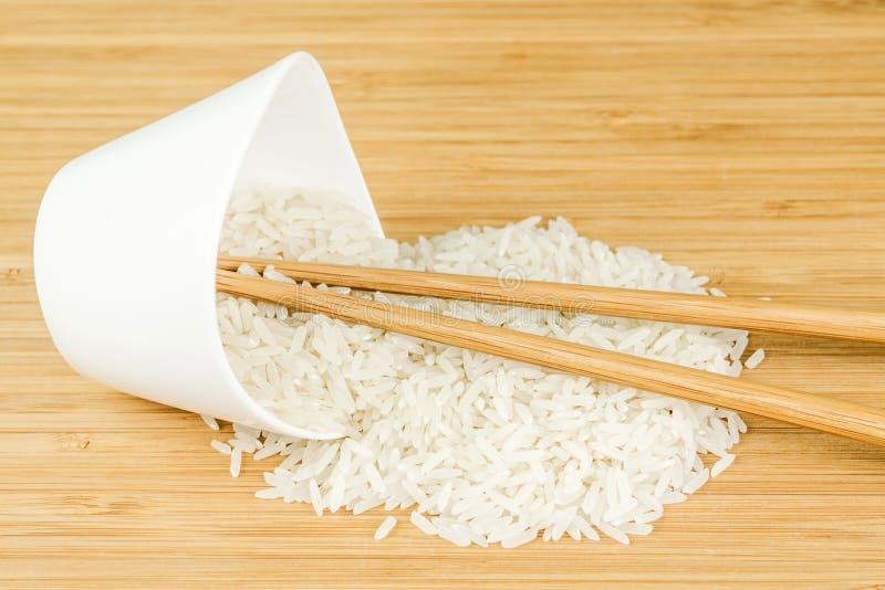 Spill för vita ris ut ur den keramiska bunken för wite med två bambupinnar royaltyfria foton
