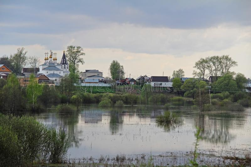 Spill the river in the fields near the village in early spring in cloudy weather. Russia royalty free stock photography