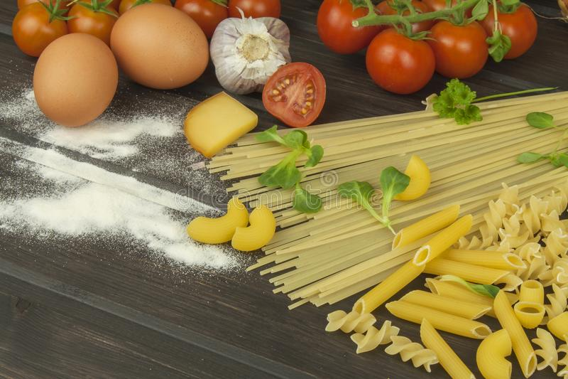 Spilled flour. Pasta and vegetables on a wooden table royalty free stock photography