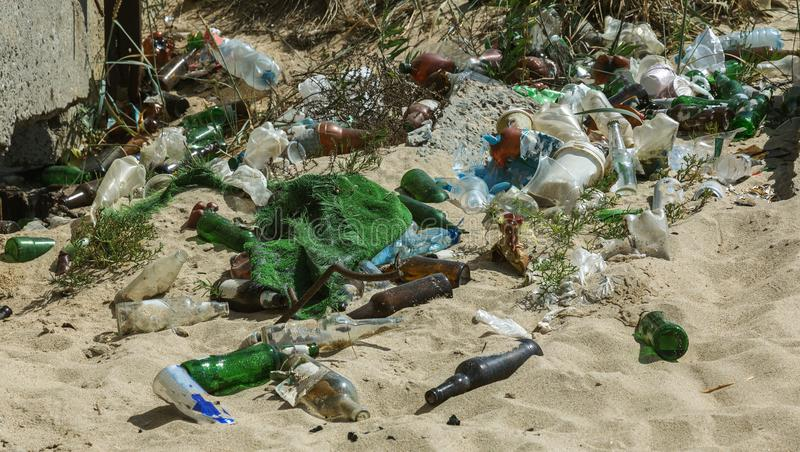Spilled garbage on beach of big city. Empty used dirty plastic bottles. Dirty sea sandy shore Black Sea. Environmental pollution. stock photography