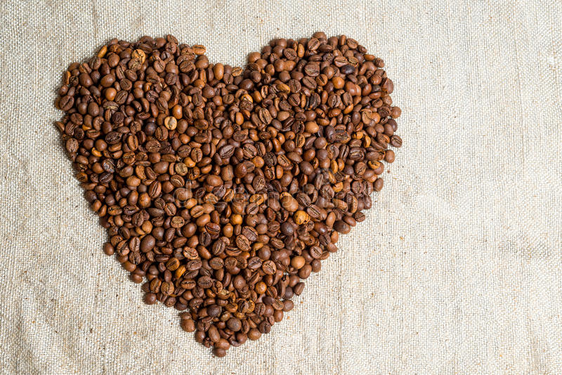 Spilled grains of fragrant coffee close-up. Photo frame, background. Heart of coffee beans. A declaration of love. stock images