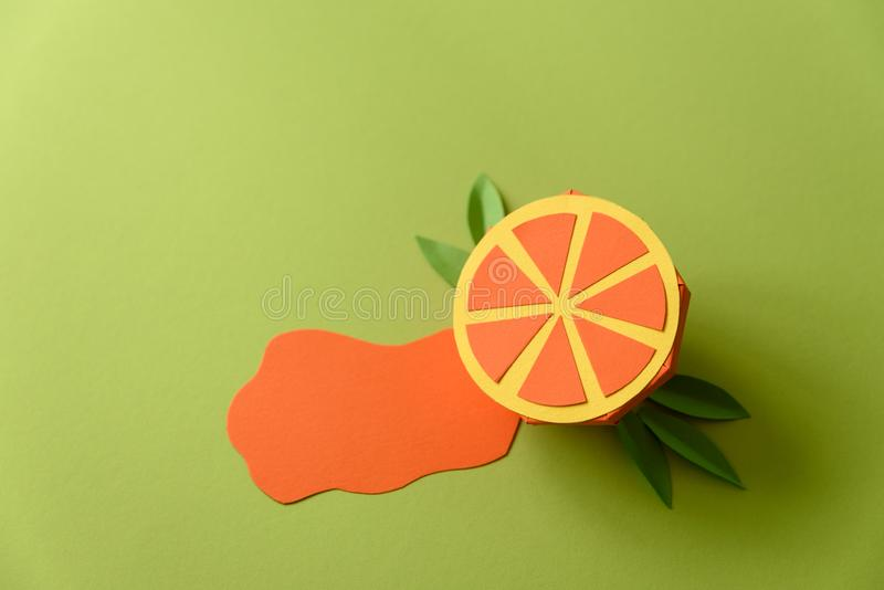 Spilled juice and paper orange fruit on green background. Copy space. Creative or art food concept.  stock images