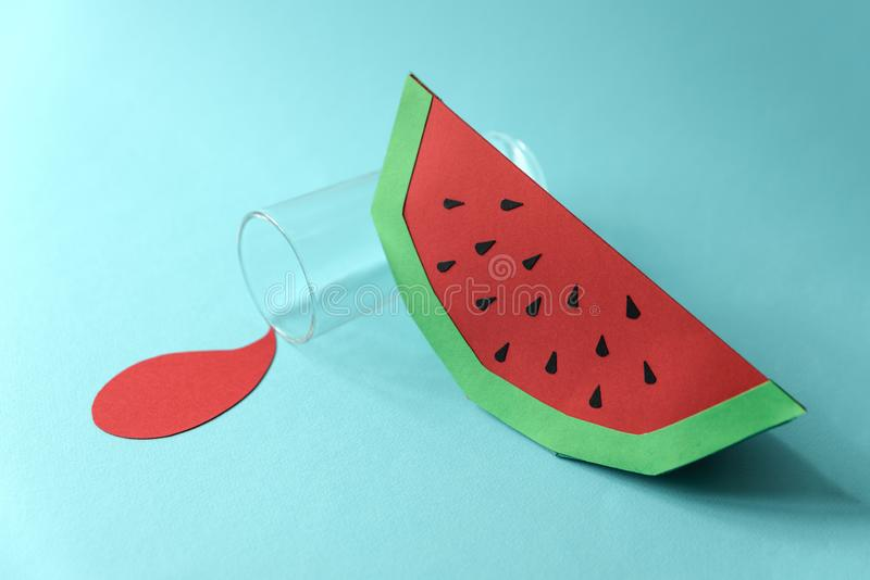Spilled juice and paper watermelon on blue background. Copy space. Creative or art food concept.  stock photography