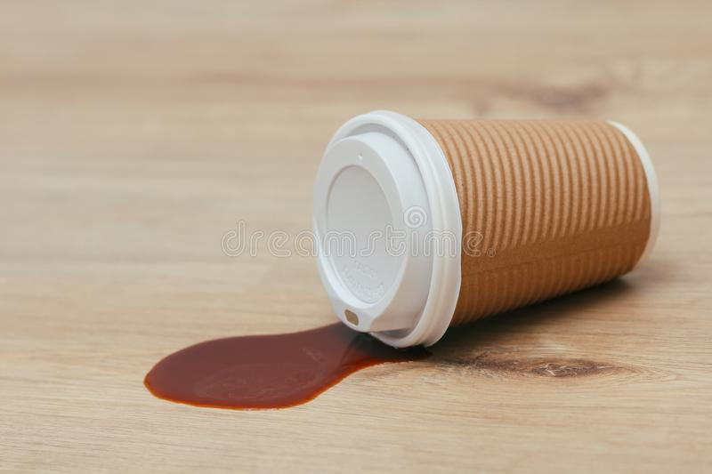 Spilled liquid on the floor. Paper coffee cup with plastic lid. Garbage. Sticky surface. Need cleaning. Sloppy man royalty free stock image