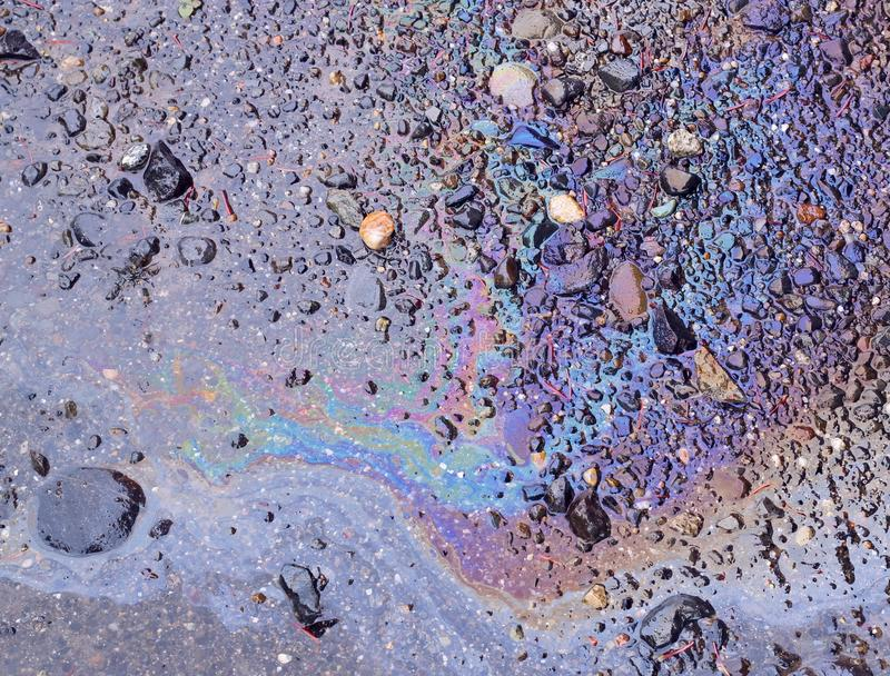 Spilled oil on wet ground. Oily sheen from spilled oil on ground wet from rain stock images