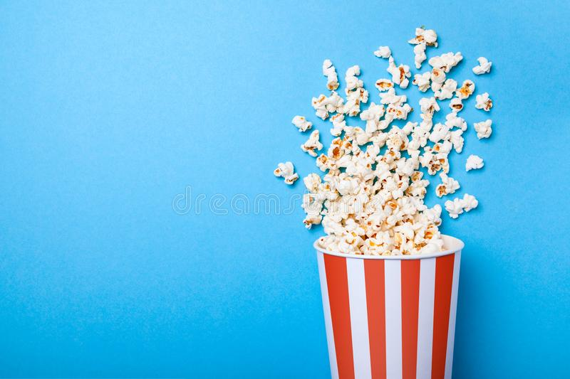 Spilled popcorn and paper bucket in red strip on blue background stock image