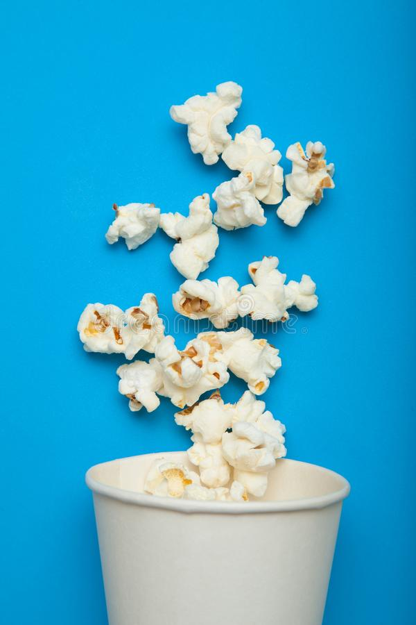Spilled popcorn from a white cup on a blue background royalty free illustration