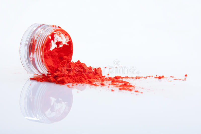 Spilled red makeup powder. From jar stock image