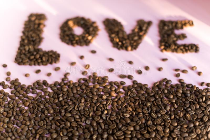 Spilled roasted coffee beans with a love inscription. stock photography