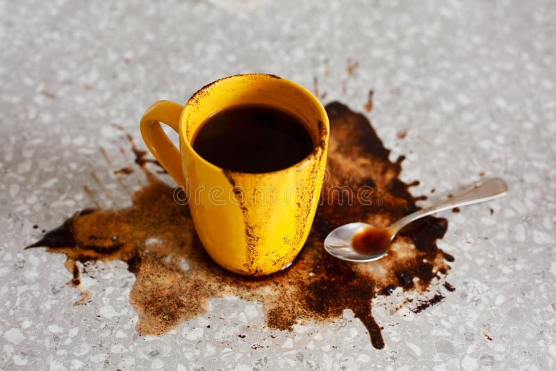 Spillt kaffe på tabellen med guling rånar och teskeden arkivfoto