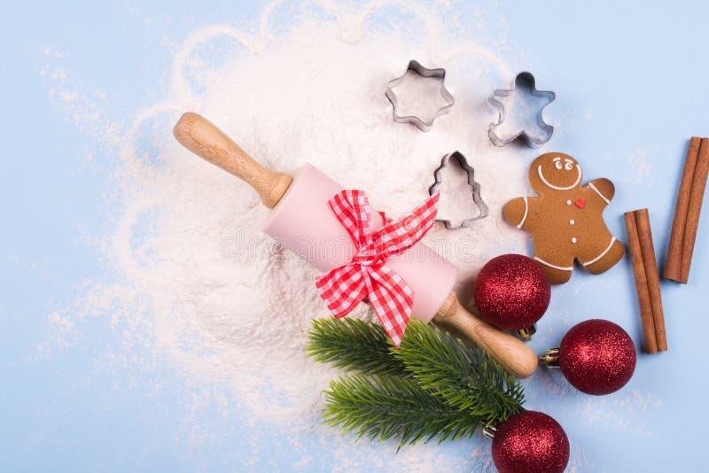 Spillt mjöl, kakaskärare, kavlen, kryddor som ler pepparkakamannen, röda garneringar för jul, sörjer filialer royaltyfri bild