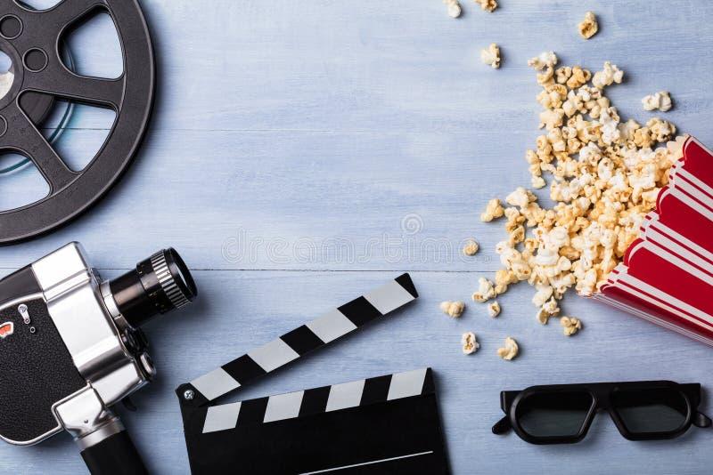 Spillt popcorn med Clapperboard och filmkameran royaltyfri foto