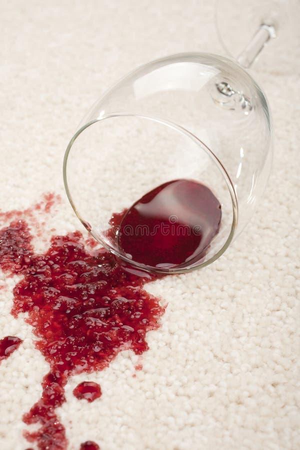 Spillt rött vin och exponeringsglas på olycka för mattförsäkringreklamation royaltyfri fotografi